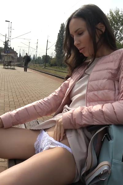 Pretty yet naughty brunette works her love hole outside on the train station