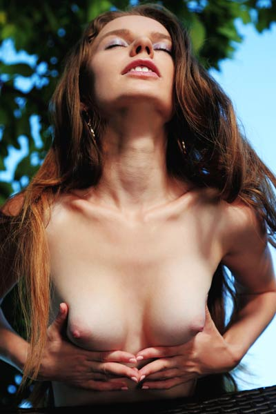 silly young babe gets naked in the garden and playfuly presents her sex assets