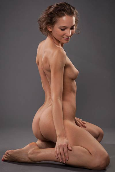 Sexy brunette vixen poses completely naked presenting her athletic body