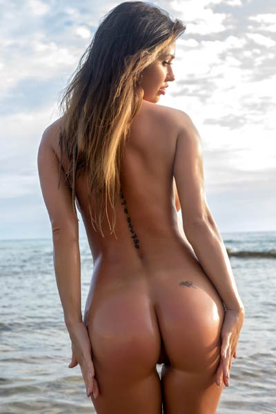 Perfectly shaped brunette poses naked on the beach showing off her peachy ass