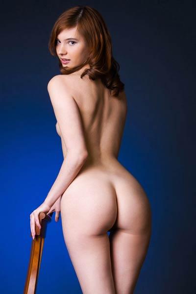 Elegant brunette babe seductively poses naked showing off her feminine figure