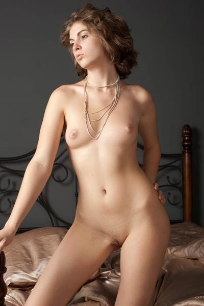 Elegant brunette babe sensually poses in the bed presenting her feminine curves