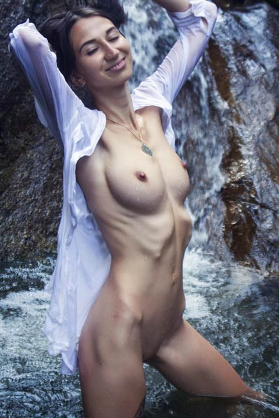 Exotic young babe exposes her fresh slender body in the mountain stream