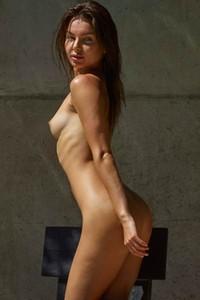 Daniela slim brunette chick is outside on the chair posing naked