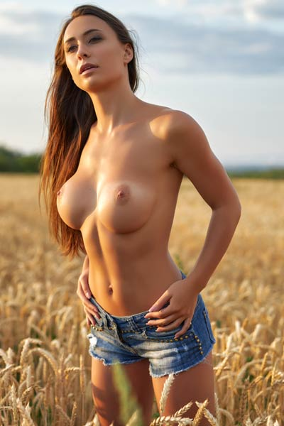 Astonishing girl is in the wheat field stripping off her denim shorts and black shirt