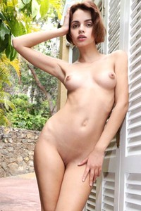 Slim doll Ariela exposing her naked body behind her house