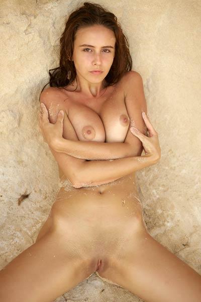 Astonishing Alisa poses naked on the sand baring her sweet assets