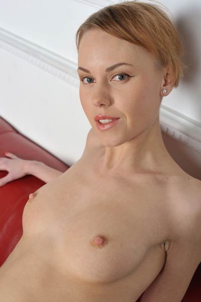Petite and foxy blonde Lena W poses completely naked on the leather sofa