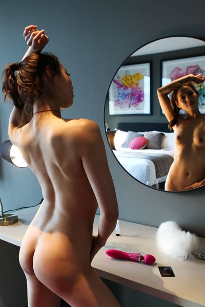 So sexy Asian babe poses naked by the mirror and presents her gorgeous tits and wet pussy