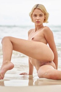 Beautiful blonde is on the beach spreading her legs revealing sweet wet pussy
