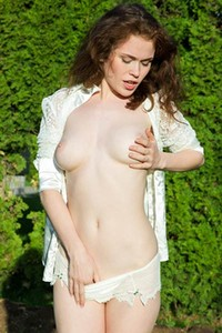 Adoring brunette shows off her nubile body as she poses in the garden