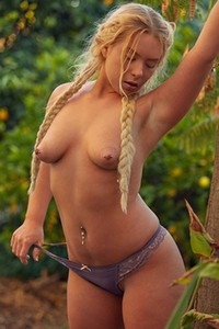 Exotic blonde babe poses naked in the forest showing off her amazing boobs and meaty ass