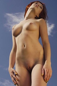 All natural redhead babe poses naked in the meadow baring her perfect small boobs and shaved pussy
