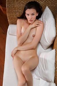 Astonishing brunette beauty poses naked on the sofa showing off her slender body
