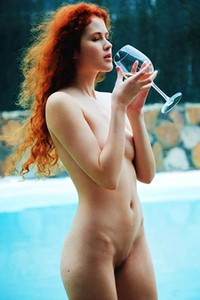 Bruning hot redhead babe Adel C exposes her sweet assets as she drinks her wine