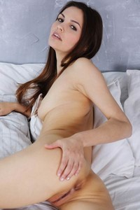 Beautiful brunette Alise Moreno spreads her legs on the bed baring her slim shaved pussy