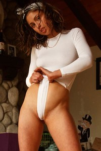 Flexible brunette with gorgeous smile stripping and posing at home
