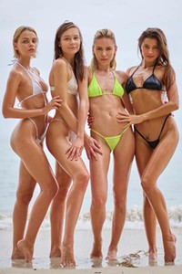 Four perfect babes get nude on the beach showing off their sweet assets