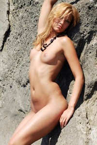 Beautiful blonde goddess exposes her perfect smooth body on the beach