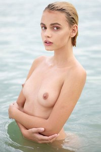 Short haired Anger Ariel poses naked in the sea baing her sweet body