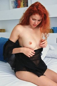 A flirty redhead hottie Adel C is on the bed pleasing herself with pussy fingering