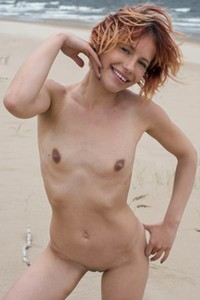Ginger beauty enjoys spending her free time totally naked outdoors on the seashore