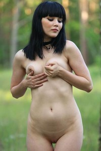 Curvy black haired babe Malena exposes her pale body in the forest