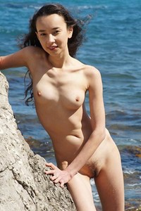 Skinny brunette is posing naked on rock beach showing us her small boobs and tight ass nicely