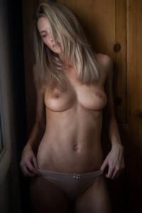 Irresistible blonde girl Courtney Lynn seductively poses naked by the wall