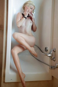 Short haired blonde is taking a shower and posing seductively waiting for you to join her