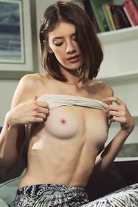Skinny young hottie with gorgeous small tits rubs her slim pussy on the couch
