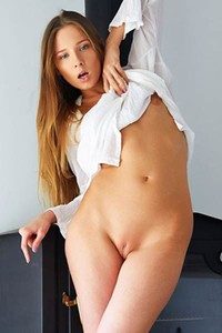 Blue eyed goddess Nimfa spreads her legs in the chair showing off her smooth pink pussy