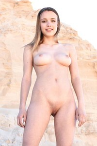 Lovely and genuine babe exhibits her magnificent smile and her slender body in the desert