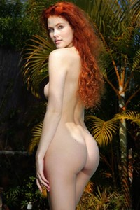 Redhead mermaid Adel C strips naked by the pool baring her elegant pale body