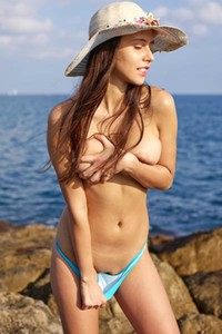 Top class brunette with hot juicy melons flashing with her attributes on the seaside