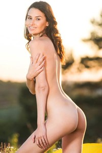 Sweet and charming babe Cristin M shows her assets outdoors in a meadow