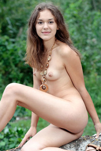Young and sweet brunette Jenya A sensually poses naked outdoors showing us her luscious tits
