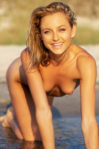 Outstanding blonde sweetie Julia displays her marvelous curves outdoors on the beach