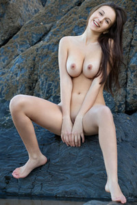 Big titted brunette Alisa I is posing fully naked on rock beach