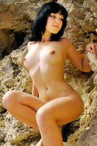 Playful dark haired hottie Kristy A poses naked on the sea rocks showing off her feminine body