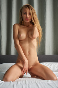Fantastic tight babe Jolie presents her perky tits and shaved pussy on the bed