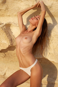 Burning hot Alice strips her white lingerie on the sandstone baring her sweet assets