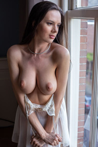 Big titted brunette Nikolart turns around and strips off her panties showing us her bouncing ass