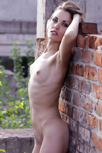 Chick in transparent pink scarf showcasing her nude body in abandoned building