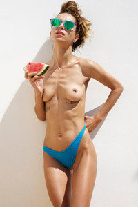Seductive tanned beauty takes off her blue bikini and poses while eating melon
