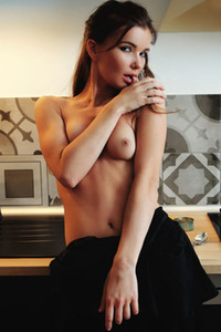 Spectacular long legged vixen is in her kitchen preparing you something special for dinner