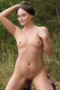 Smoking hot brunette vixen delightfully poses naked in nature