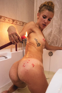 Lustful slender babe drinks wine in the bathtub and plays with hot wax