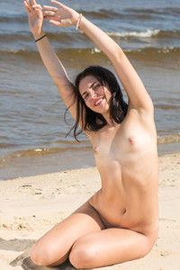 Hot brunette Zhenya Mille is posing naked on the beach showing us her small tits and well shaped ass