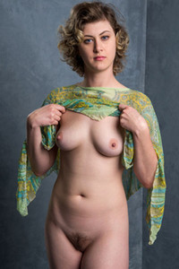 Short haired brunette Dani pulls up her shirt and shows us her medium and perky boobs
